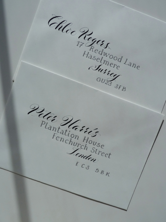contrasting-calligraphy-styles-black-ink-on-white-envelopes