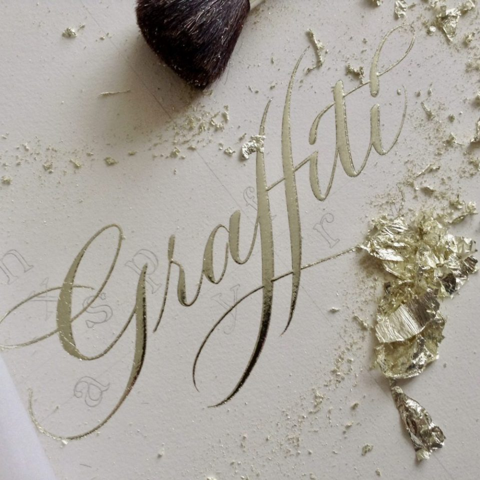 gilding the word graffiti work in progress with real loose leaf gold
