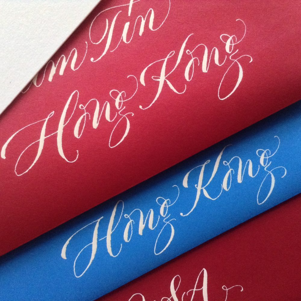 white copperplate calligraphy on red and blue envelopes.