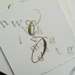 gilded minuscule g with genuine gold leaf