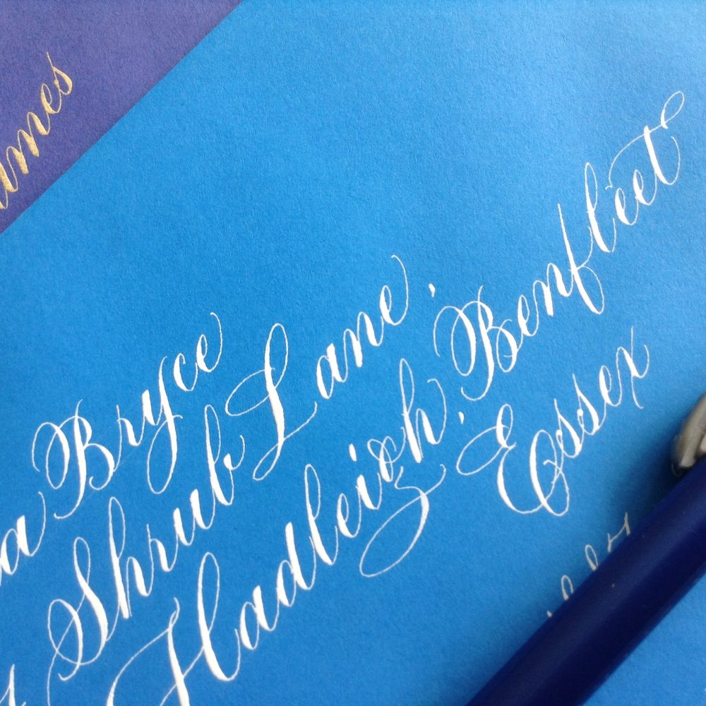white-copperplate-variation-script-on-blue-envelope-uk